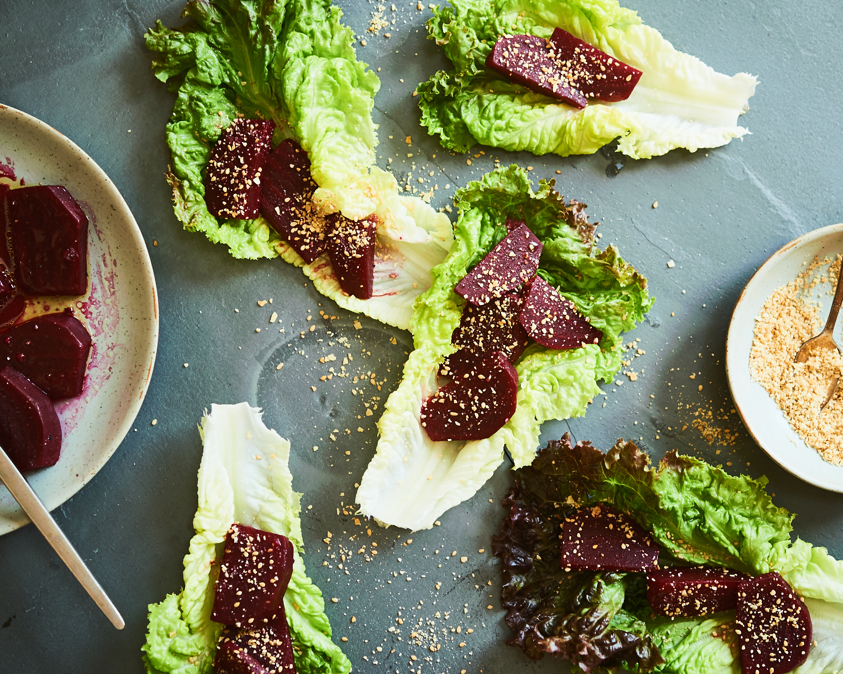 This salad is made with marinated beets and sesame seeds and lettuce leaves and slivered almonds.