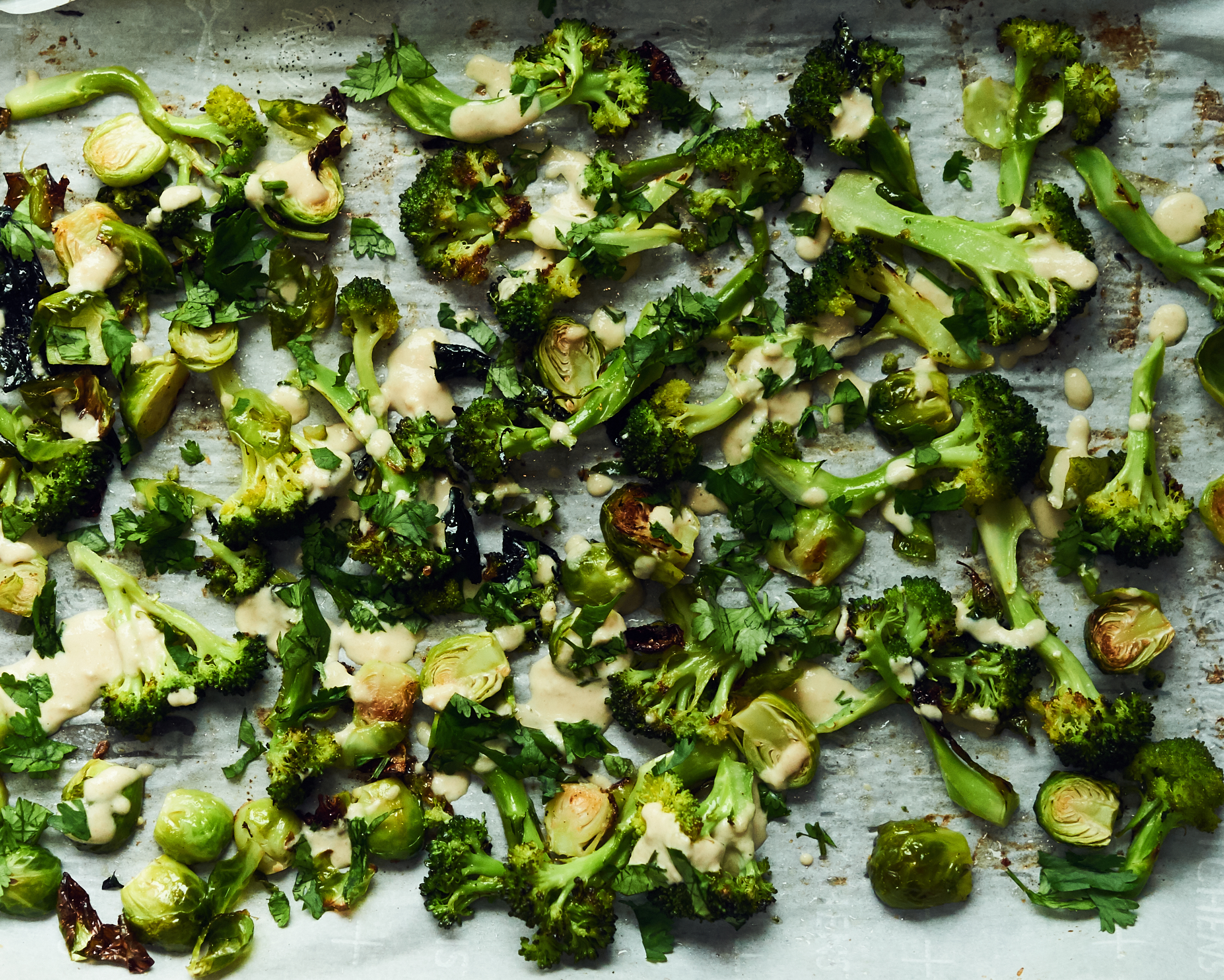 This is a photo of roasted broccoli and Brussels sprouts with tahini lemon drizzle. These veggies are all good for cancer prevention.